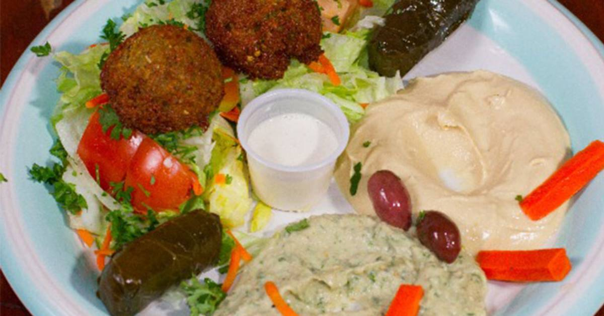 a dish with falafel, hummus, and more on it