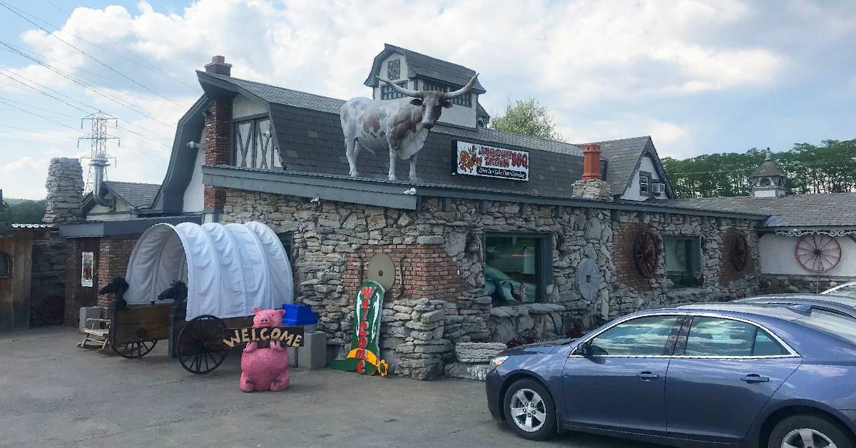 outside a restaurant with steer statue on roof, a covered wagon entrance, and a pig statue with a welcome sign