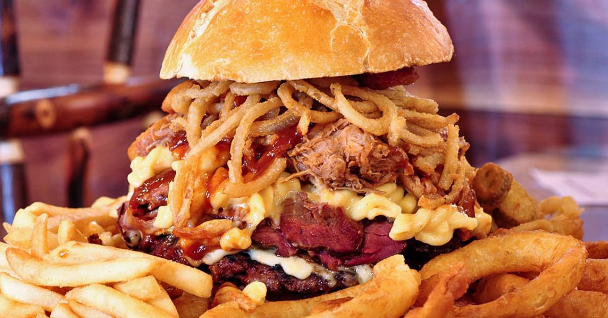 large burger with onion rings, mac and cheese, fries, and more