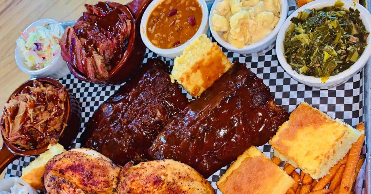 overhead photo of bbq ribs, cornbread, chicken, brisket, and other sides