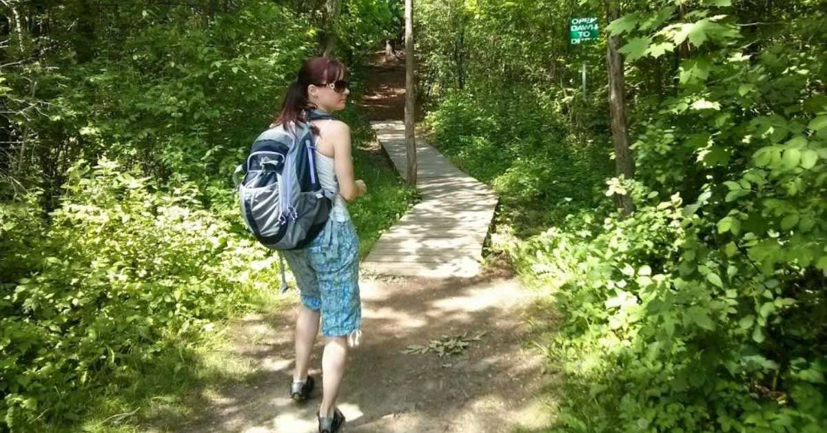 woman with back[ack on trail
