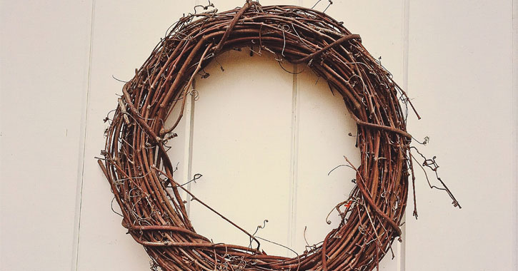 a plain wreath from sticks hanging on a door