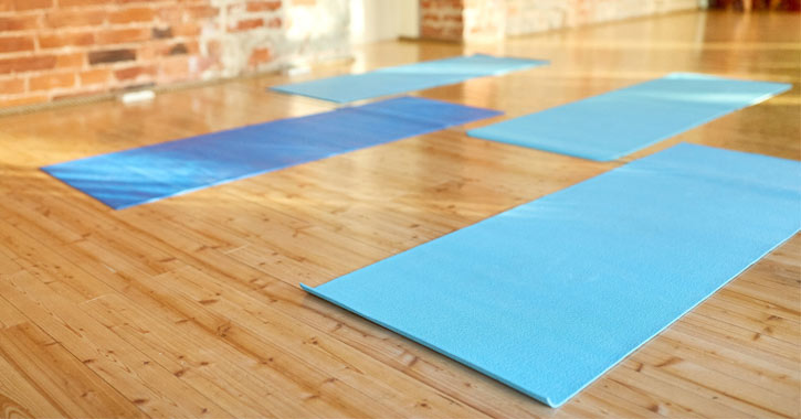 four yoga mats on a wooden floor
