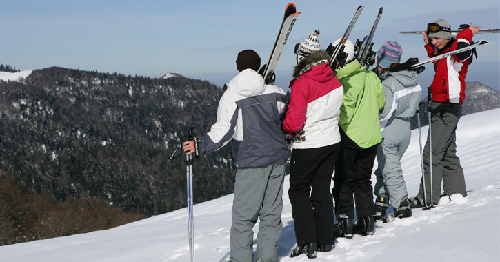 a group of young people in ski gear looking out onto the mountain
