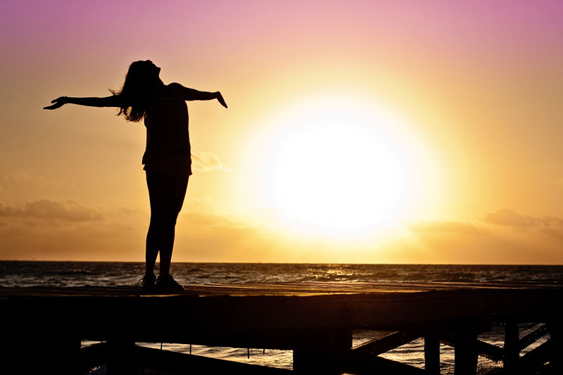 Woman with arms outstretched standing on a beach at sunset