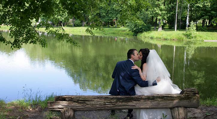 wedding couple kissing by pond