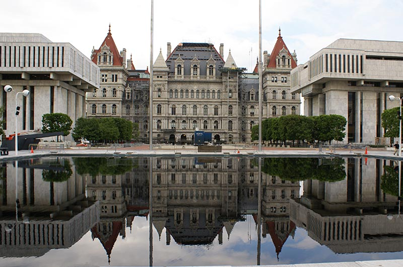 albany capitol building with reflection on water