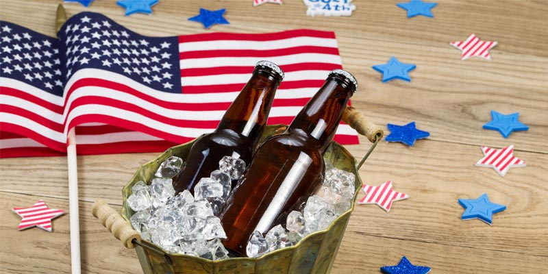 two American flags on a table with an ice bucket with two beers in it and star decorations scattered in different shades of blue and red and white stripes