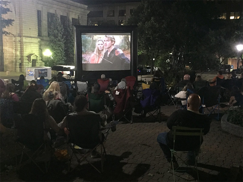 Crowd sits outside watching the movie The Princess Bride on a screen