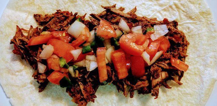 an open burrito with beef and pico de gallo salsa