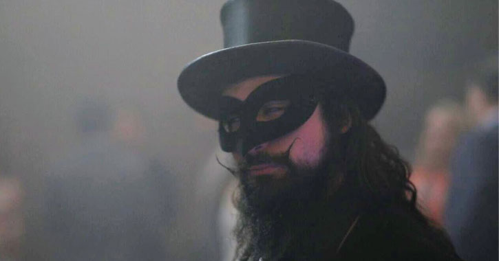 a masked man in a top hat with a beard