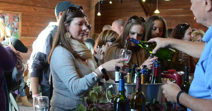 a woman receiving wine at a wine tasting