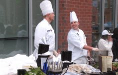 chefs at an event talking and laughing behind their table