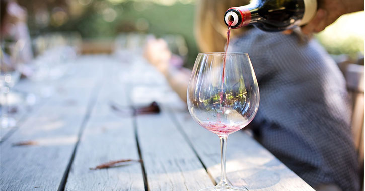 red wine being poured into a wine glass on a coffee table with a few leaves on it