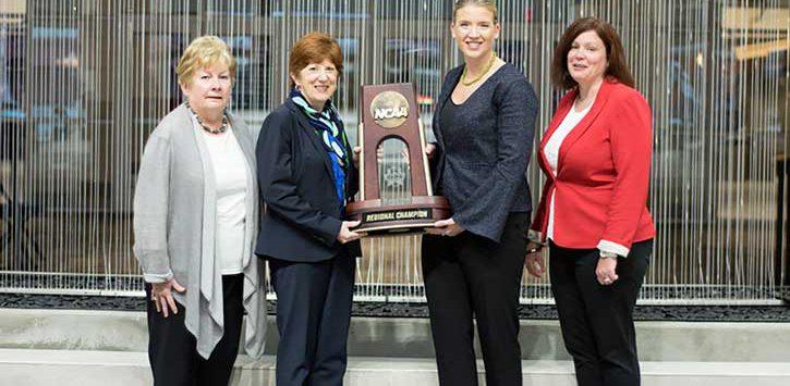 Women leaders from Albany NY holding NCAA trophy