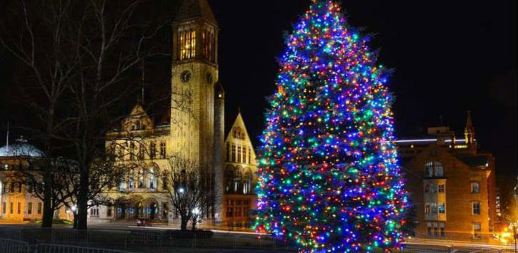 a lit Christmas tree with colored lights next to a building