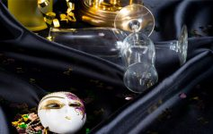 a masquerade mask next to an overturned champagne glass