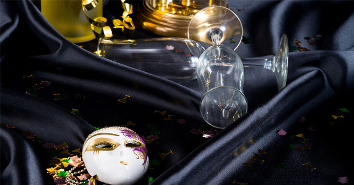 a masquerade mask next to two overturned champagne glasses
