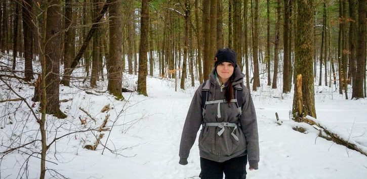 a woman hiking in the wood in winter