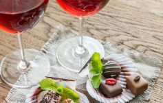 two glasses of a reddish wine in front of gourmet chocolates