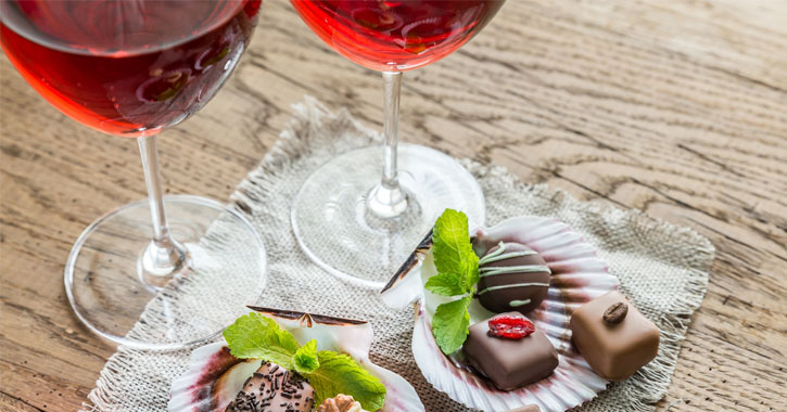 two glasses of a reddish wine next to gourmet chocolates