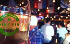 glass of Nine Pin cider in the foreground, crowd in background