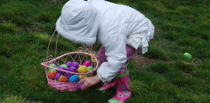 a little girl in a white coat doing an Easter egg hunt