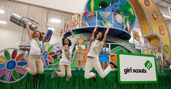 three Girl Scouts jumping in front of a large float