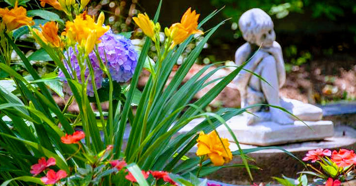 flowers in foreground, statue in background in garden