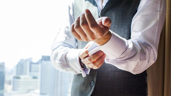 man putting on cufflink