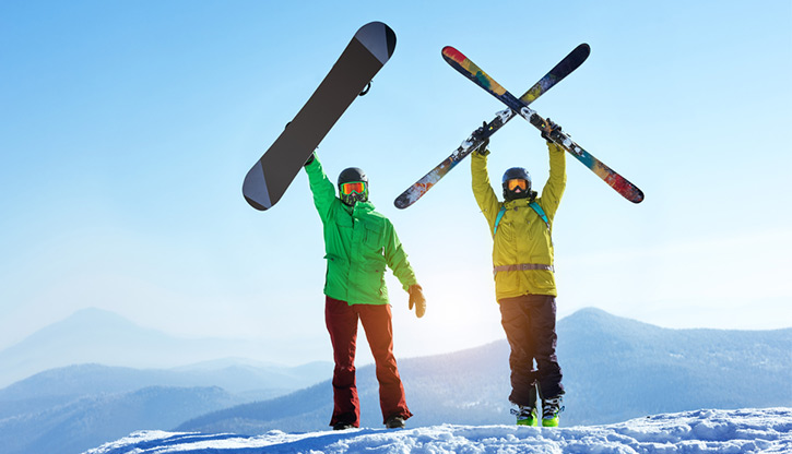 skier and snowboarder on top of a mountain