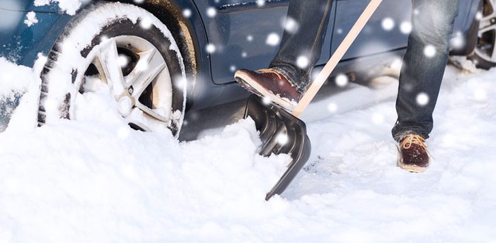 a person shoveling snow near a car