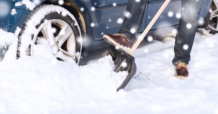 a person shoveling snow near a car