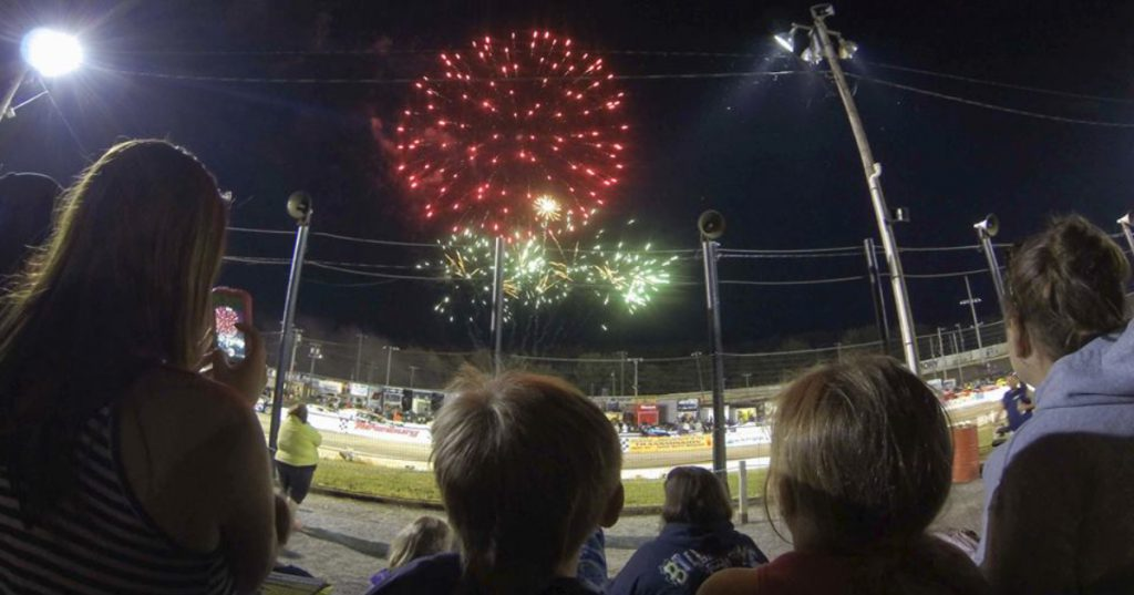 group of people watching fireworks at a speedway