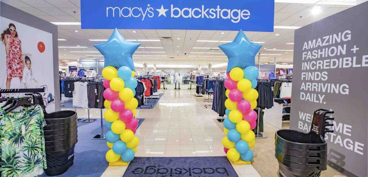 a banner and balloons mark the entrance of a new macy's backstage location
