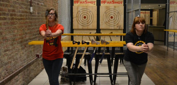 women practicing axe-throwing at far shot