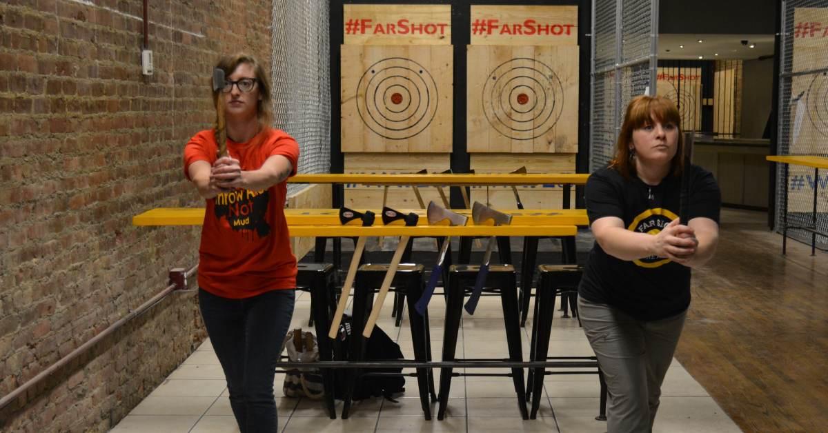 women practicing axe-throwing at far shot