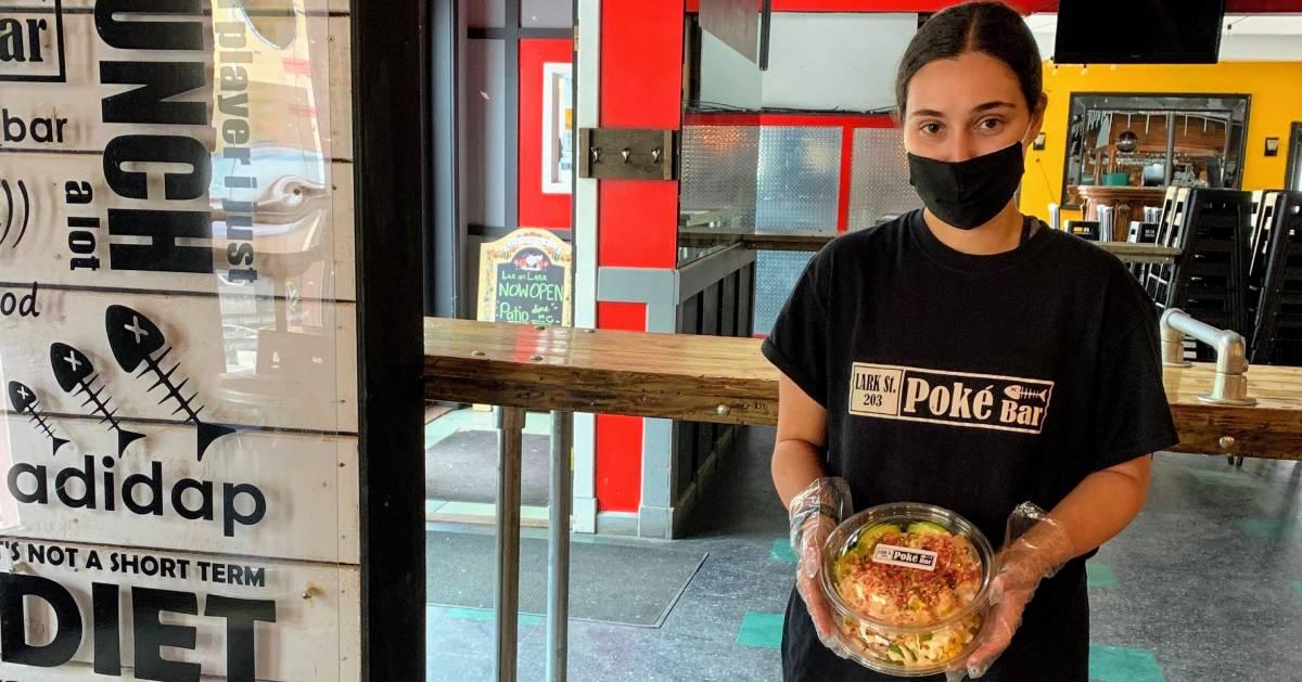 woman with Lark Street Poke Bar shirt on holding poke bowl