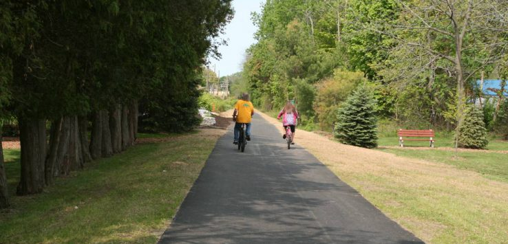 two people biking down a paved trail