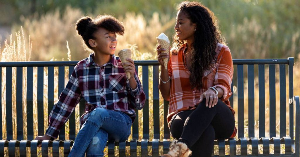 young girl and young woman sitting on a bench with ice cream
