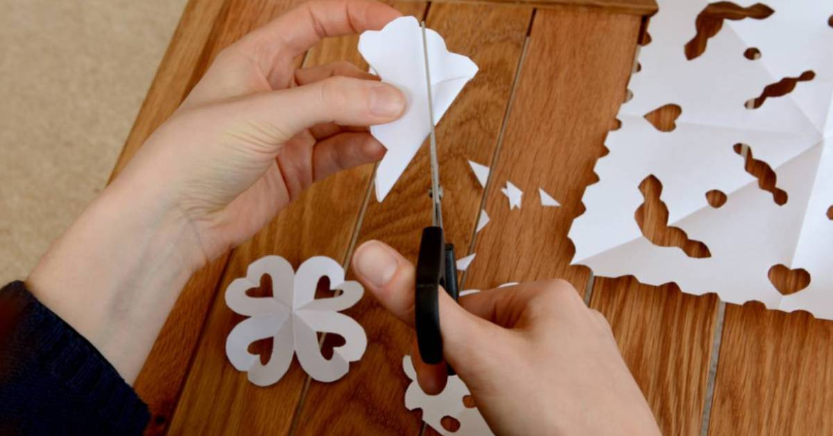 person cutting paper into snowflake shape
