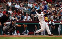baseball player swinging bat with crowd in the stands