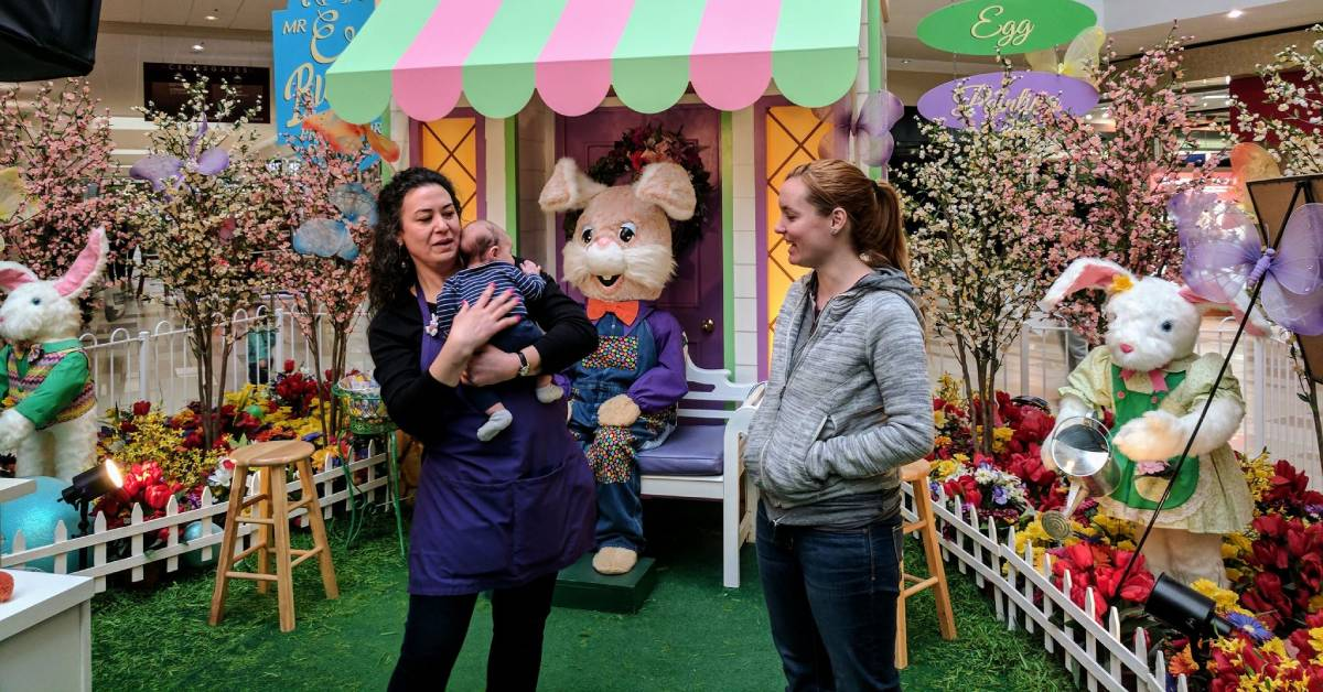 two women, a baby, and an easter bunny at an easter themed area