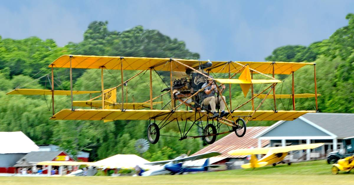 man flying a historic yellow airplane