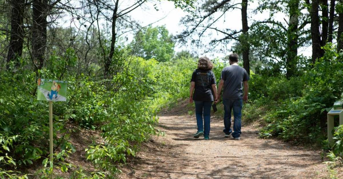 man and woman walking on a nature trail